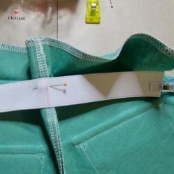 Marquer l'élastique en son milieu. Epingler l'élastique sur l'envers de la valeur de coulisse, placer son bord supérieur le long de la pliure de la coulisse et aligner ses extrémités avec les lignes de couture des cotés et son milieu avec la couture du milieu-dos. Batir à la machine extrémités et milieu