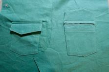 Epingler les rabats au dessus des poches. Les piquer à 12 mm au-dessus du bord supérieur des poches. (dégarnir les marges). Replier les rabats vers l'endroit de façon à cacher les coutures et surpiquer les coutures d'assemblage.